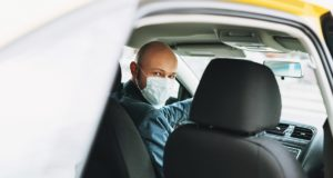 Bald man taxi driver in medical face mask inside yellow car looks at camera. Concept of coronavirus quarantine