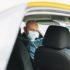 Bald man taxi driver in medical face mask inside yellow car looks at camera. Concept of coronavirus quarantine
